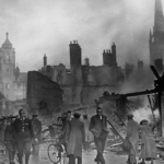 """Photograph – Luftwaffe bombardment of Coventry (from BBC History, http://www.bbc.co.uk/history/events/the_blitz). Caption: """"People in Coventry walk to work past smouldering piles of rubble after a bombing raid in 1940."""""""